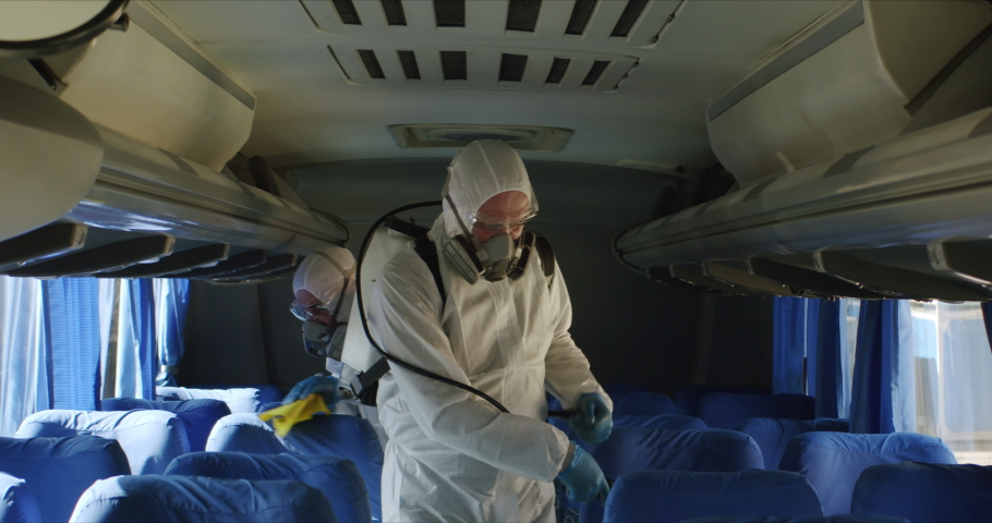 HazMat team in protective suits decontaminating public transport tourist bus interior during virus outbreak Royalty-Free Stock Footage #1048813870