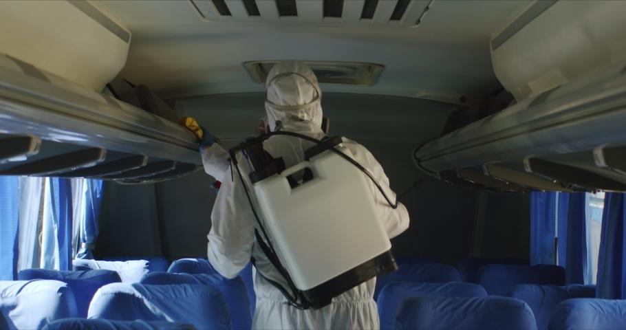 HazMat team in protective suits decontaminating public transport tourist bus interior during virus outbreak, coronavirus, COVID-19 Royalty-Free Stock Footage #1048813885