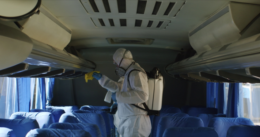 HazMat team in protective suits decontaminating public transport tourist bus interior during virus outbreak Royalty-Free Stock Footage #1048813894