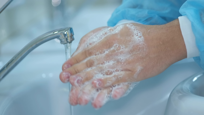Close-up of hand washing. The doctor washes his hands with soap and running water. Correct way to wash hands according to the World Health Organization. Protection against coronavirus (COVID-19). | Shutterstock HD Video #1048814239