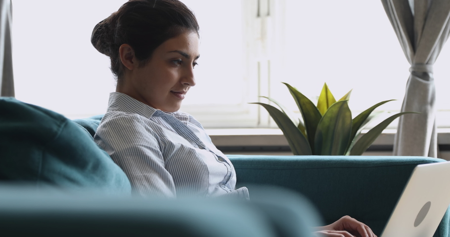 Side view concentrated millennial indian woman working on computer, sitting on comfortable couch remotely at home. Focused professional communicating with clients or web surfing information online.