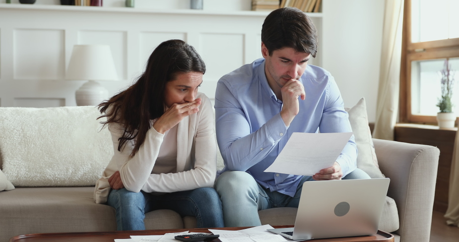Frustrated young adult couple feeling stressed about high mortgage rates doing paperwork at home. Angry husband and wife renters calculating household payments, having financial problems or bank debt.