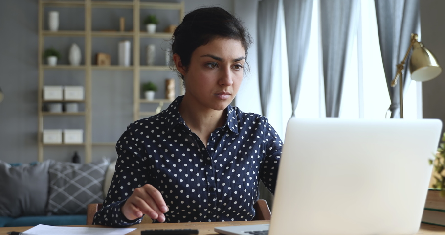 Focused serious young indian woman using computer accounting applications, calculating domestic utility bills, managing monthly budget finances, paying banking loan online, sitting at table in home. Royalty-Free Stock Footage #1048820542