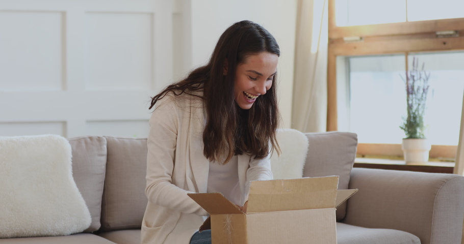 Excited young woman customer opening parcel box at home. Amazed happy girl shopper unboxing fashion purchase sitting on couch. Satisfied female consumer unpacking postal shipping delivery concept