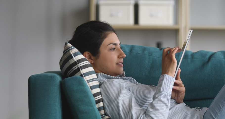 Side view happy young indian woman lying on cozy sofa, studying design apps on digital computer tablet. Motivated millennial hindu designer drawing sketches, smiling girl editing photos alone at home. | Shutterstock HD Video #1048820572