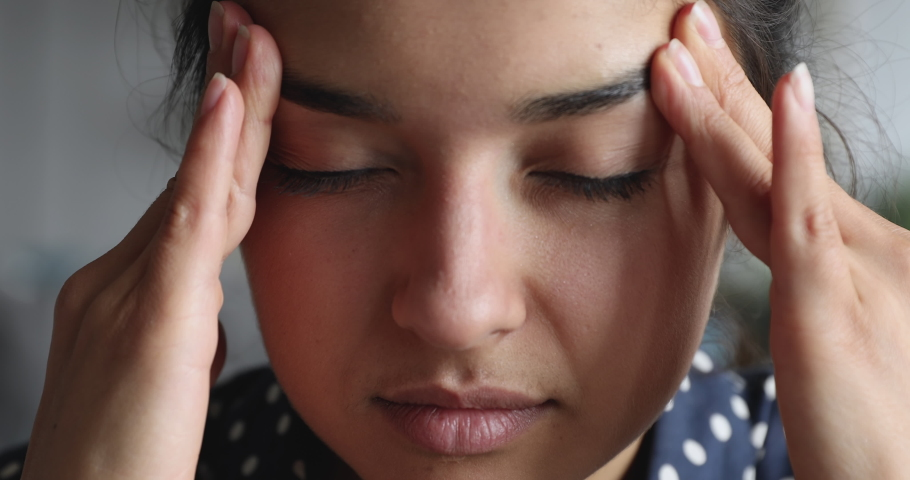 Close up exhausted frustrated young indian woman massaging nose bridge temples. Stressed unhealthy millennial mixed race girl feeling tired suffering from migraine, panic attack, high blood pressure. | Shutterstock HD Video #1048820629