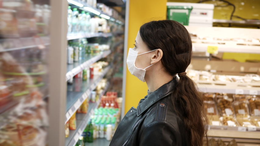 Beautiful brunette young woman in medical masks at supermarket. pandemic. Selects products. | Shutterstock HD Video #1048835185
