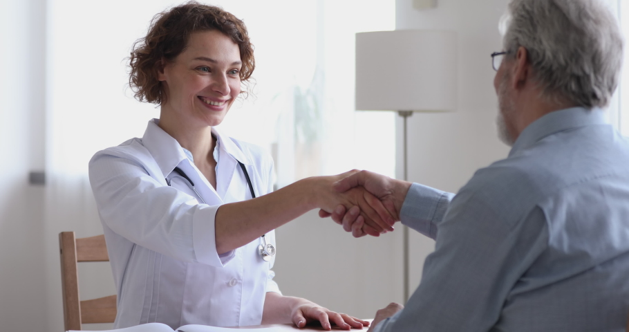 Smiling friendly female physician giving healthcare advice handshaking senior adult male patient. Happy doctor and older client shake hands at medical office expressing respect, gratitude and trust.