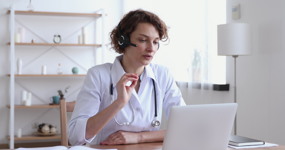 Female medical assistant wears white coat, headset video calling distant patient on laptop. Doctor talking to client using virtual chat computer app. Telemedicine, remote healthcare services concept. | Shutterstock HD Video #1048839271