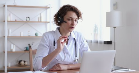 Female medical assistant wears white coat, headset video calling distant patient on laptop. Doctor talking to client using virtual chat computer app. Telemedicine, remote healthcare services concept.