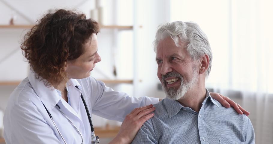 Caring kind female doctor embracing reassuring happy senior patient. Young surgeon or nurse helping smiling old healthy grandpa at nursing home. Elderly medicare, healthcare, homecare medicine concept