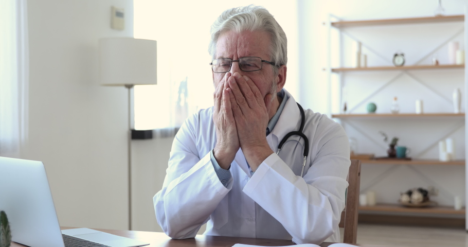 Worried upset senior old adult male doctor feels depressed regrets medical malpractice sitting alone in office. Desperate sad elder surgeon thinking of grief, suffering from burnout or guilt concept.   Shutterstock HD Video #1048839283