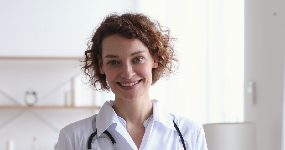 Happy young european woman doctor wearing white medical coat and stethoscope looking at camera. Smiling female physician posing in hospital office. Positive general practitioner close up face portrait