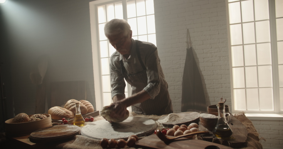 Professional senior moustached caucasian baker working in bakery shop in morning, kneading dough for bread, using traditional recipes, elderly man enjoying his hobby after retiring 4k footage | Shutterstock HD Video #1048841497