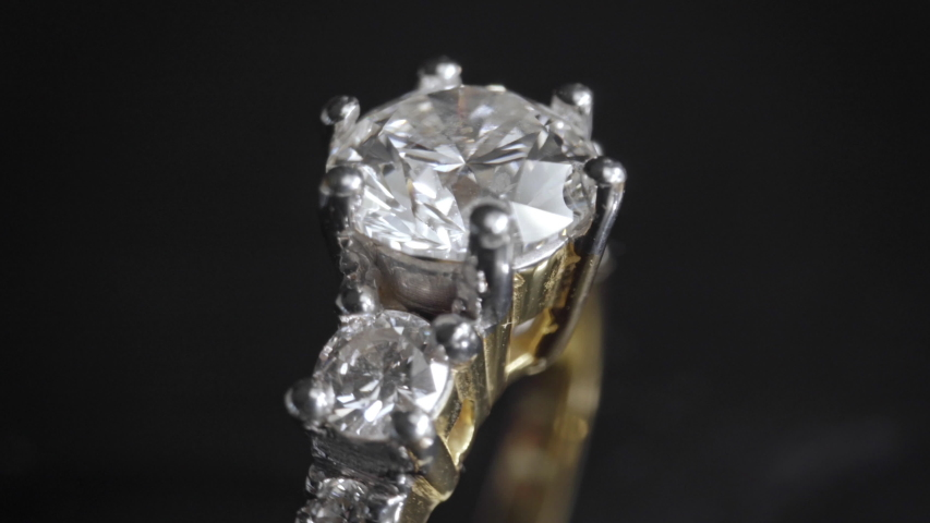 Extreme detailed of diamond ring close up shot while rotating on dark background. The wedding ring was shot using macro lens with shallow depth of field. Engagement, marriage and wedding concept. | Shutterstock HD Video #1048842685