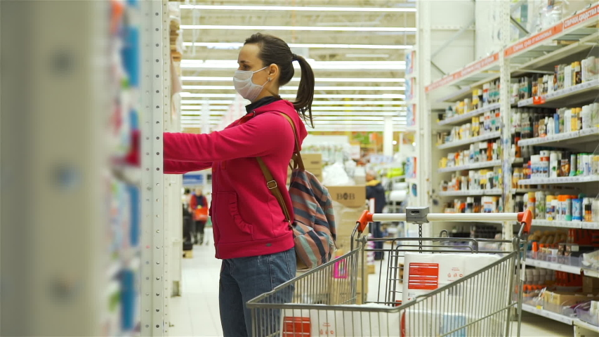 Woman in Medical Protective Mask Shopping for Toilet Paper in a Shopping Mall. Covid-19 spreading Outbreak. Health, Safety, Pandemic Concept | Shutterstock HD Video #1048843801