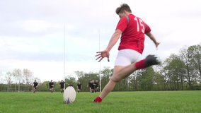 Scoring a conversion with a Rugby Kick. A player is kicking the Unbranded ball during a match through the rugby posts. Super Slow motion. Stock Video Clip Footage
