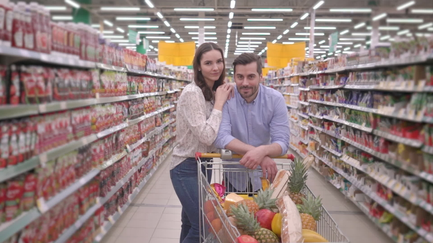 Attractive happy young millennial family couple shopping in supermarket with shopping cart, looking at camera and smiling, lovely husband and wife buyers customer satisfaction grocery store concept