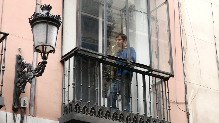 A neighbor from the center of Madrid playing the saxophone on the balcony of his house locked up by the state of alarm in Spain by COVID-19. Filmed on March 23, 2020.