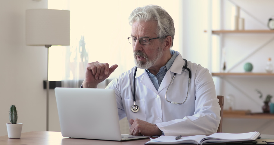 Older doctor talking to patient making video call on laptop. Senior male physician speaking looking at pc screen communicating by webcam in web chat consulting client online. Telemedicine concept