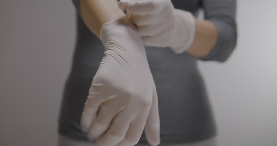Woman putting on white gloves, her lower torso in the back | Shutterstock HD Video #1048879009