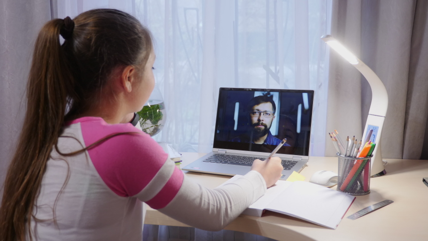 Schoolgirl video chatting with a teacher at home during the coronavirus epidemic in the city. Distance education concept, on-line education at home. | Shutterstock HD Video #1048897126