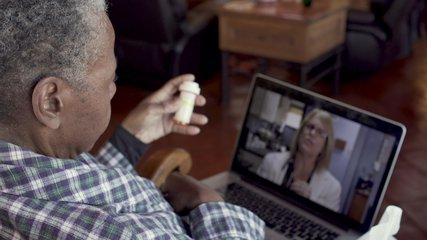 Sick elderly black woman talking to her female doctor about her prescription medication through a video chat telemedicine session - OTS