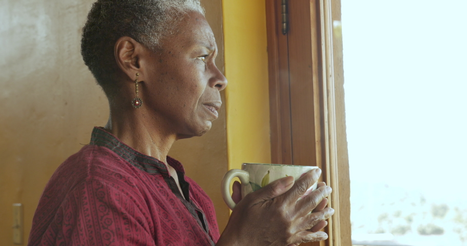 Concerned worried mature African American black woman holding a hot steaming tea or coffee cup looking out a window