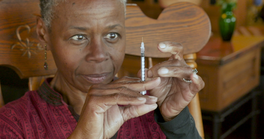 Older black senior woman with a needle and insulin syringe giving herself an injection for treatment of her diabetes - close up | Shutterstock HD Video #1048900897