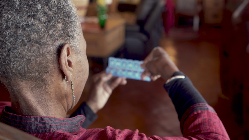 Older black woman closing her daily pill dispenser after filling it with her prescription medicine as a reminder to remember to take her drugs - rack focus from person to organizer