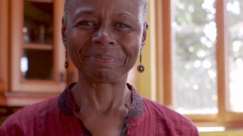 Smiling happy mature senior African American black woman in her home pointing at the camera rack focus from her face to the tip of her finger