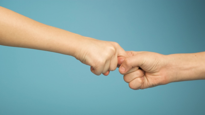 Two human hands touching each other with point fingers isolated on blue background. | Shutterstock HD Video #1048913146