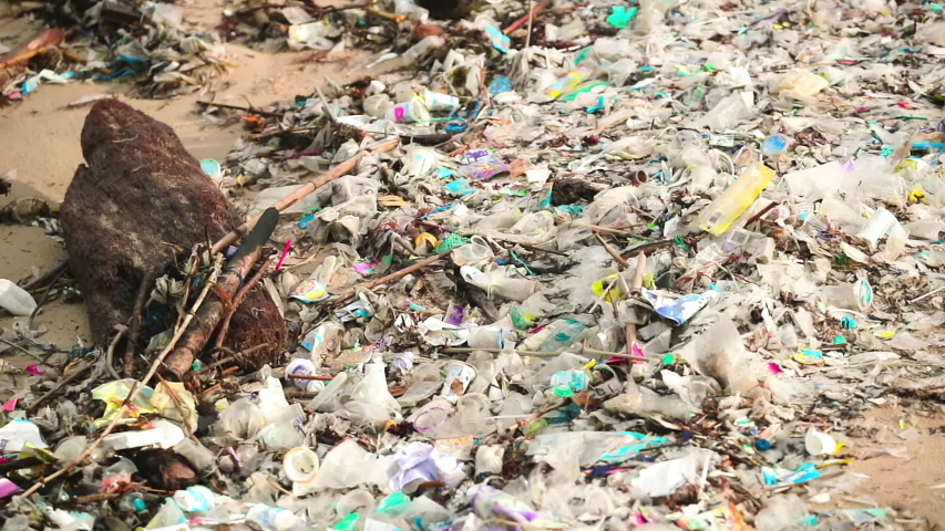 Slow motion. The worlds most polluted beach in Bali. Plastic bags bottles and paper trash on the sandy dirty beach. Sea waves full of litter hitting the beach. Huge dump in tropical paradise. | Shutterstock HD Video #1048916263