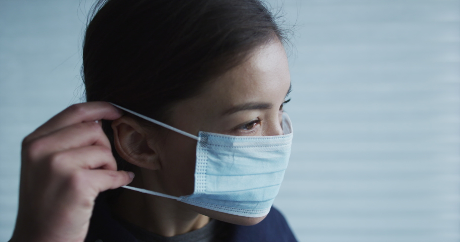 Woman putting on surgical face mask for protection against coronavirus SARS-CoV-2. SLOW MOTION on RED Cinema camera. | Shutterstock HD Video #1048916443