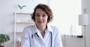 Female doctor wears headset speaking looking at web cam providing remote medical assistance in virtual chat. Medic worker video calling consulting patient online. Telemedicine concept. Webcam view