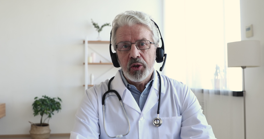 Senior male doctor wears white medical coat, stethoscope, headset makes distant video call. Old adult physician talks to camera consulting patient online in web chat. Telemedicine concept. Webcam view