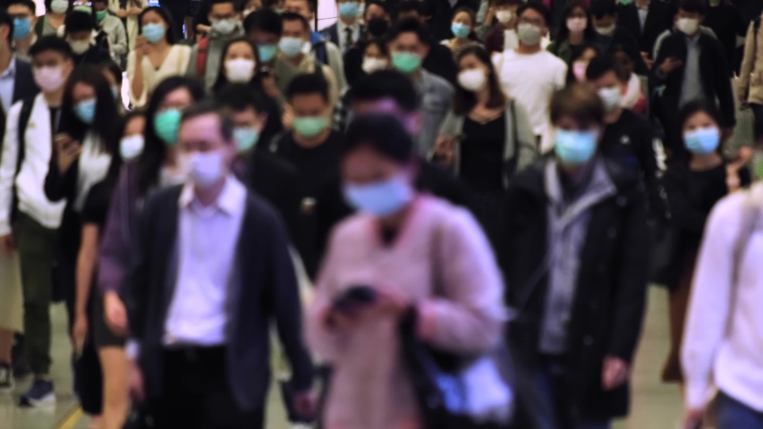 Slow motion of unrecognized people wearing medical face masks at metro in Hong Kong. Coronavirus concept