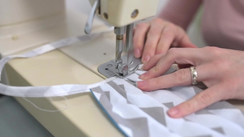 Woman hands using the sewing machine to sew the face medical mask during the coronavirus pandemia. Home made diy protective mask against virus. | Shutterstock HD Video #1048929358