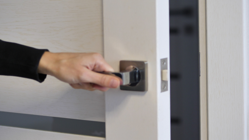 Woman hand opening and close white wooden door in office. Holding door handle. Full HD video motion | Shutterstock HD Video #1048933606