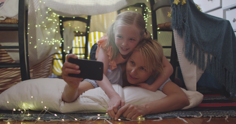 Happy Caucasian woman enjoying family time with her daughter at home together, smiling and talking in a tent in a sitting room, using a smartphone, taking selfie with her daughter, social distancing