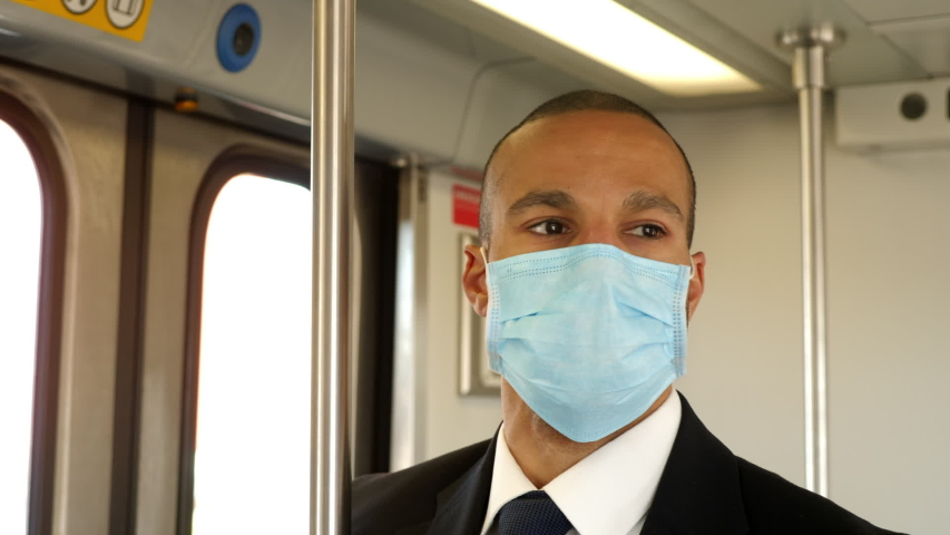 Businessman in a suit rides train to work while wearing a face mask to protect from getting sick | Shutterstock HD Video #1048952083