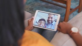 Rear view of young woman relaxing on couch while talking to her husband and son using digital tablet at home. Mature middle eastern man and child communicate through video chat on laptop. Happy family
