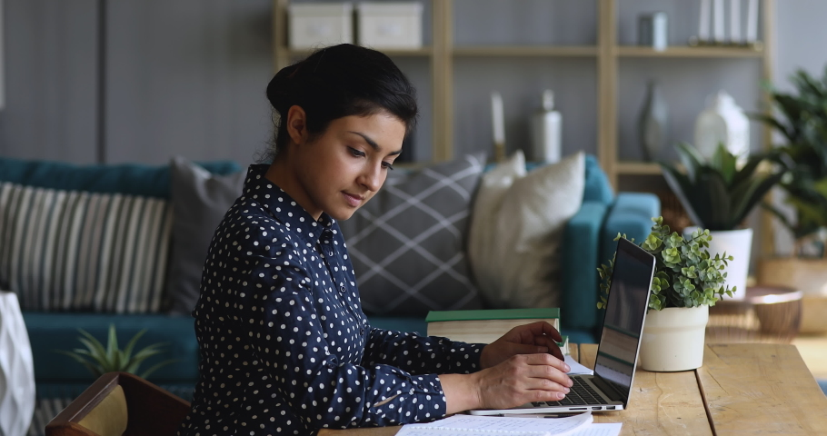 Side view concentrated millennial indian female college student woman doing university assignment or homework alone at home, using academic paper notes, doing educational project, sitting at table. Royalty-Free Stock Footage #1048972123