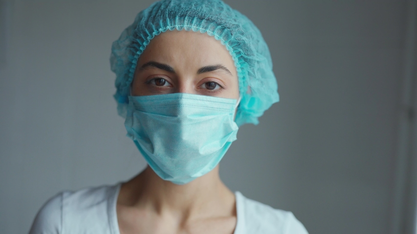 Portrait of a female doctor or nurse wearing medical cap and face mask looking at the camera on grey background. Ready to receive patients in hospital. Health care, medical concept. | Shutterstock HD Video #1048978357
