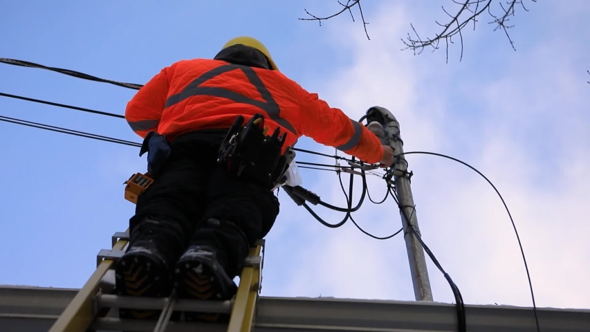 A telecoms operative man is seen working from a ladder on a utility pole, wearing high visibility personal protective clothing, high viz PPE, and hard hat Royalty-Free Stock Footage #1048984168