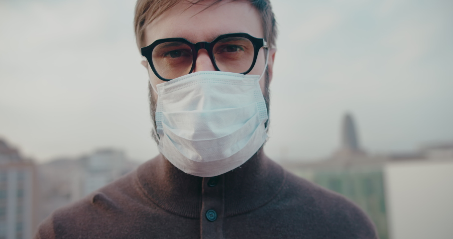 Young man takes off medical mask. Breathes deeply and smiling looking at camera on blurred background. Health care and medical concept. Safety life,COVID19 coronavirus,healing virus,stop pandemia. | Shutterstock HD Video #1048984630