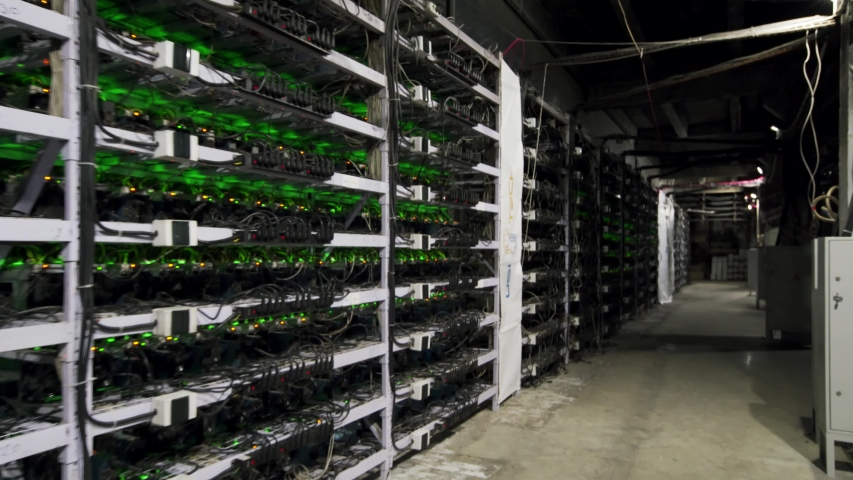 Cryptocurrency mining equipment on large farm. ASIC miners on stand racks mine bitcoin in server room. Blockchain techology application specific integrated circuit. Steadycam footage along racks. | Shutterstock HD Video #1048996147