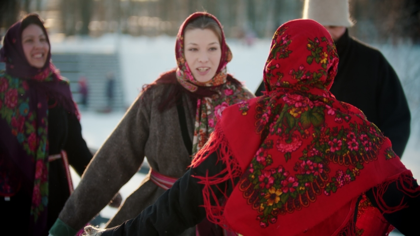 Russian folklore - people in bright clothes in the winter in the park are dancing folk dances Royalty-Free Stock Footage #1048999324
