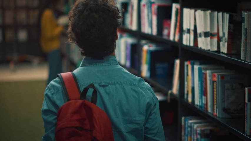 University Library: Student Walks Between Rows of Bookshelves Searching for the Right Book Title for Assignment and Exam Preparations. Back View Following Slow Motion Camera Shot. Young People Study Royalty-Free Stock Footage #1048999492
