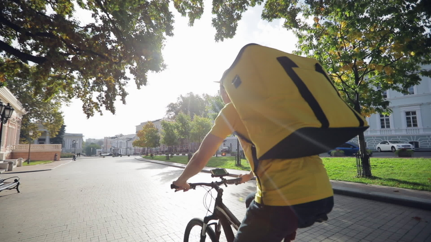The city courier service, the courier in a yellow T-shirt with a yellow thermal backpack rides a bicycle, the video shot is from the back.